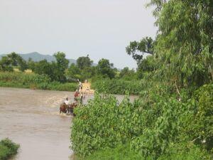 Leute waten durch den Fluß
