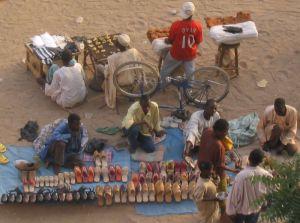 Hier werden Schuhe aus Kunststoff und aus Leder verkauft, in der Reihe dahinter gibt es Kolanüsse und getrocknetes Fleisch.