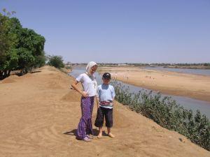 Bernice und Timon stehen auf dem Deich am Fluss Logone.