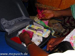 offener Koffer, prüfende Hände