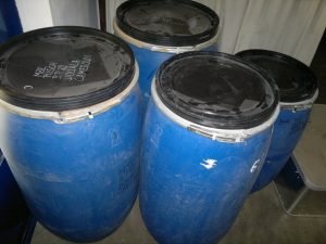 Vier blaue Fässer aus Kunststoff, mit großen schwarzen Deckeln.